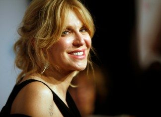 Courtney Love sonriendo con un vestido negro