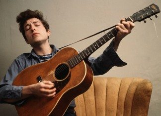 Bob Dylan tocando la guitarra en un sillón en 1963