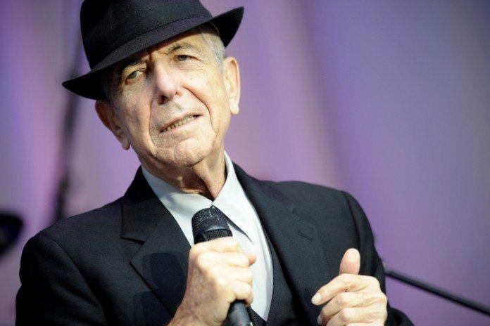 Leonard Cohen con un sombrero, un micrófono en la mano y un fondo morado
