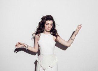 Lorde con vestido blanco y las manos alzadas.