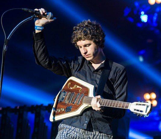 Luke Pritchard de The Kooks sostiene el micrófono y la guitarra en directo