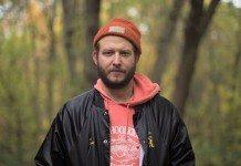 Justin Vernon en un bosque con un gorro naranja en el anuncio de Red Wing de 2014