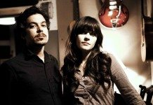 She & Him con colores ocre y un guitarra en la pared