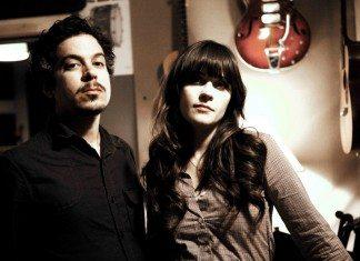 She & Him con colores ocre y un guitarra en la pared