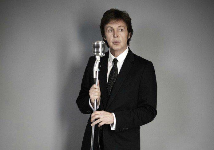 Paul McCartney con un micrófono en una pared gris