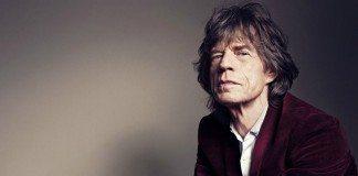 Mick Jagger sentado con un pared gris