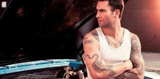 Adam Levine en un coche con el capó abierto