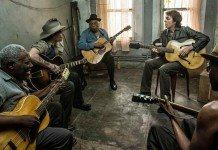Johnny Depp y Paul McCartney tocando la guitarra en una habitación.