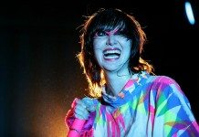 Karen O con un vestido de colores y un micrófono rosa
