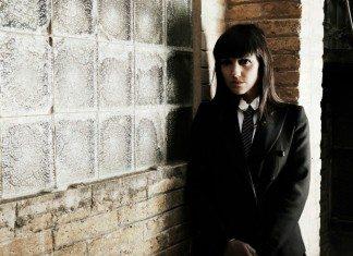 La Bien Querida vestida de traje en una pared.