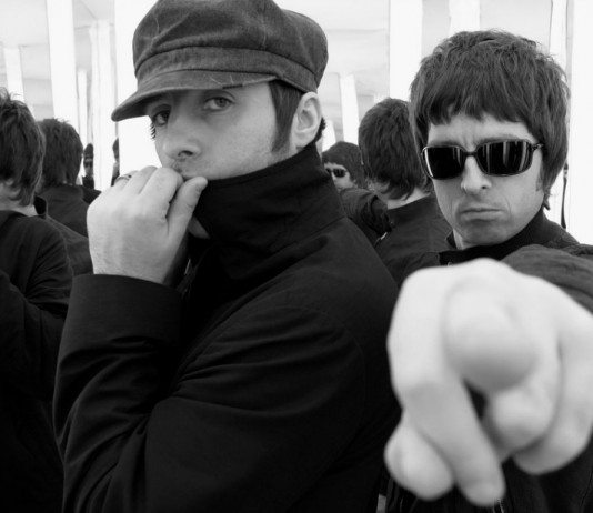 Noel Gallagher señala a la cámara junto a Liam Gallagher.