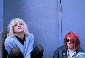 Courtney Love y Kurt Cobain posando en un muro azul
