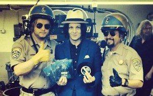 Jack White junto a dos policías con la grabación de Lazaretto.