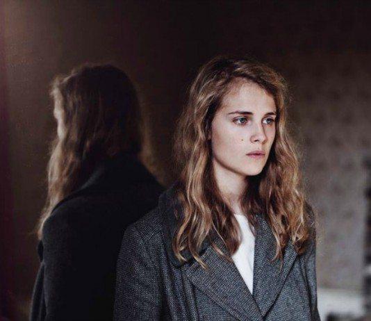 Marika Hackman con un abrigo frente a un espejo