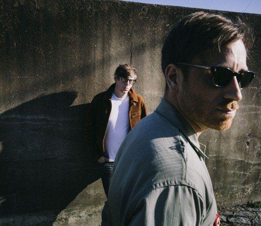 Dan Auerbach con gafas de sol y Patrick Carney en un muro de piedra (The Black Keys)