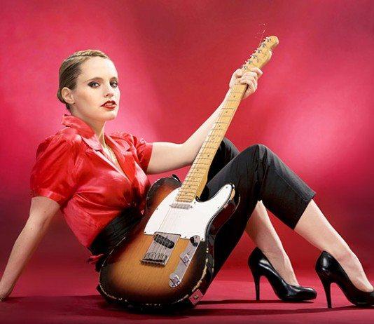 Anna Calvi con una guitarra Telecaster en un fondo rojo