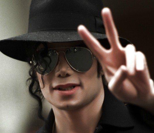 Michael Jackson con gafas y sombrero haciendo el símbolo de la paz
