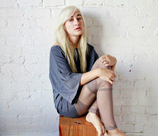 Zola Jesus sentada en una pared de ladrillos blancos