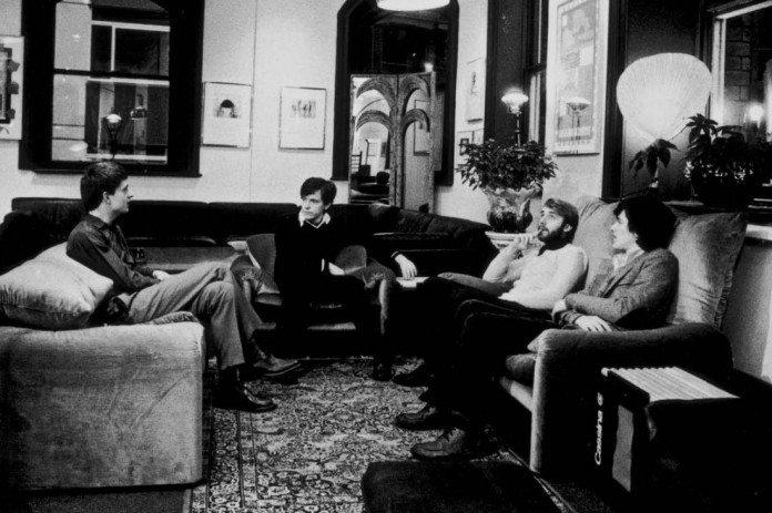 Joy Division sentados en unos sofás en un hall.