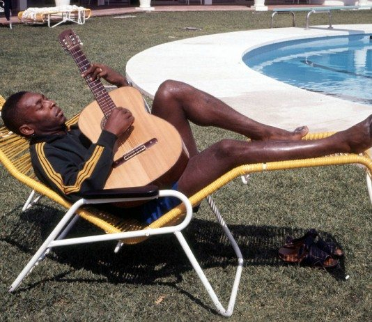 Pelé tocando la guitarra en una hamaca al lado de una piscina