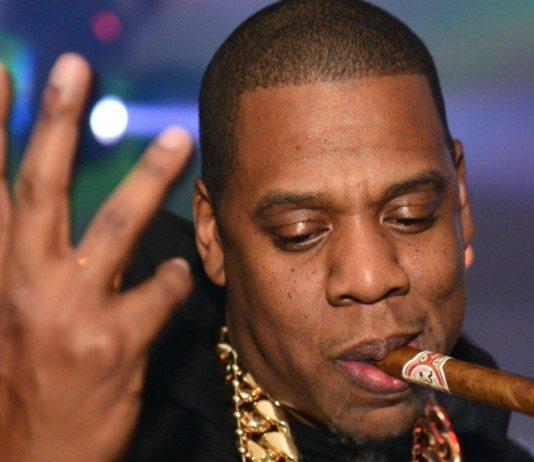 Jay Z con un puro y la mano en alto