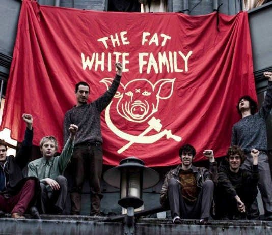 The Fat White Family alzan el puño junto a su bandera roja.