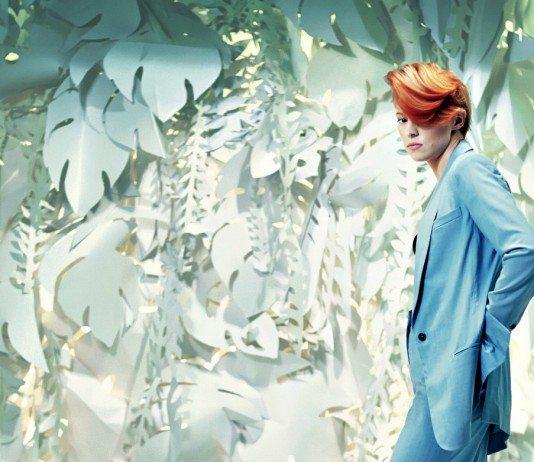 La Roux con traje azul de fondo plantas de papel blanco.