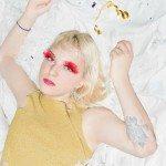 Lowell tumbada en una cama con pestañas postizas rojas.