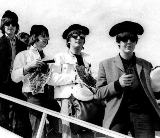 The Beatles bajando de un avión en España con montera.