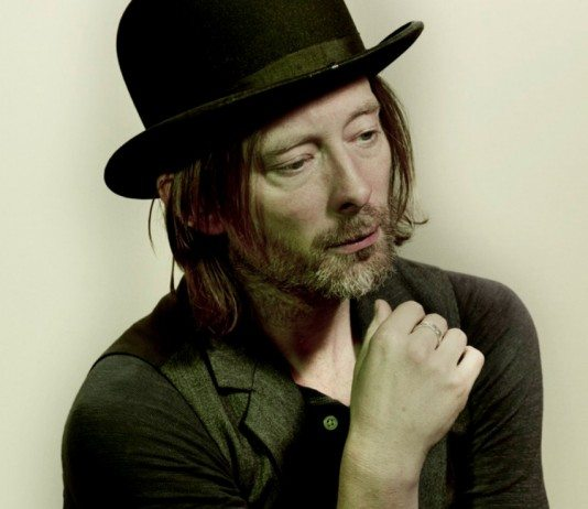 Thom Yorke con un sombrero se pone la mano en la cara.
