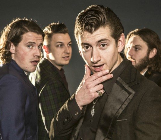 Arctic Monkeys con Alex Turner enfocado y un fondo oscuro