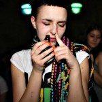 Chica inhalando de un tarro en un festival.