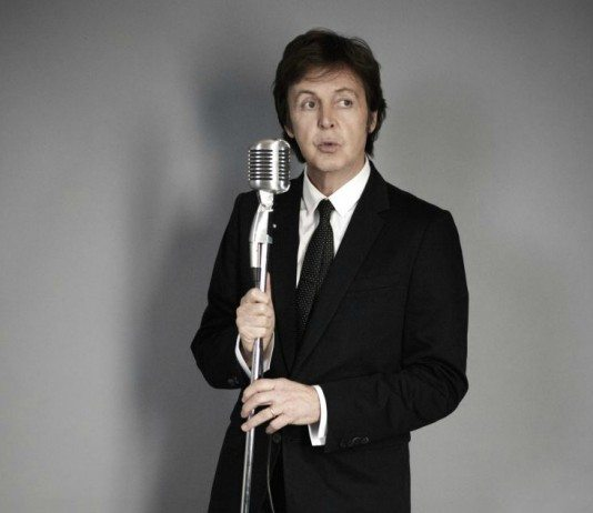 Paul McCartney con un micrófono en una pared gris
