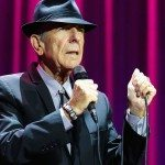 Leonard Cohen con un micrófono frente a un telón morado