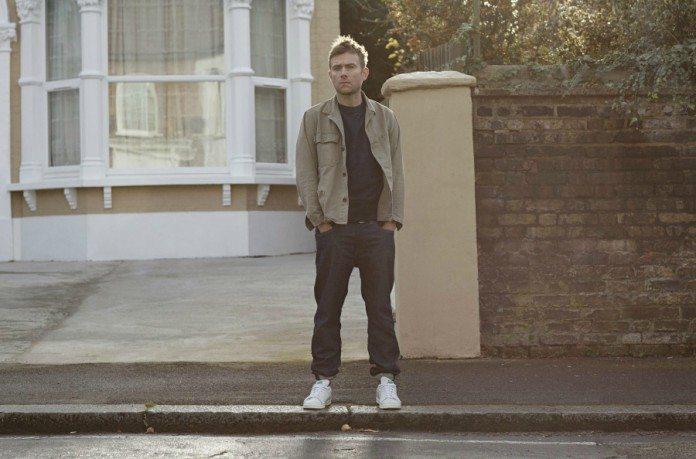 Damon Albarn en la acera, delante de una ventana blanca