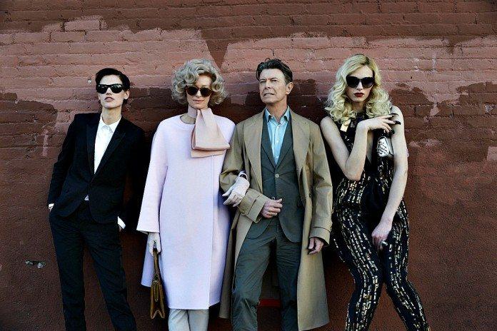 David Bowie junto a tres mujeres en una pared roja.
